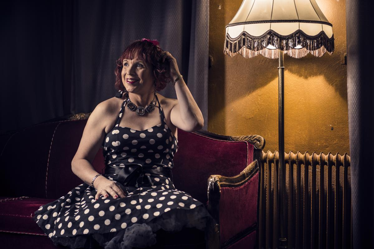 Jaana istuu pallomekossa punaisella sohvalla
