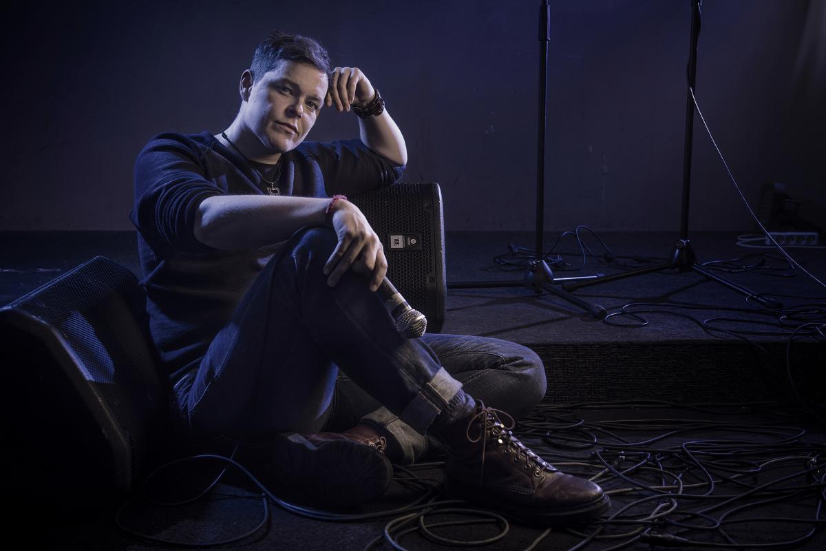 Jamie standup-lavan edessä mikrofoni kädessään