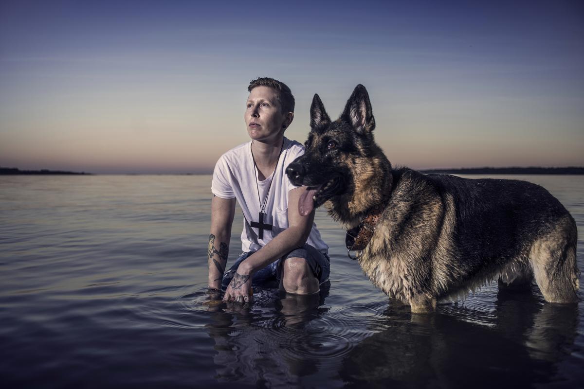 Venni koiransa kanssa meren rannalla auringon laskiessa